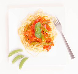 Spaghetti with pea and bacon sauce, decorated with basil