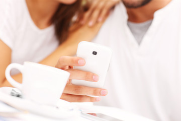 Closeup of hands and smartphone in a cafe