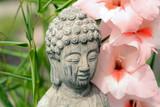 Fototapety Boeddha in  bamboe tuin met bloemen