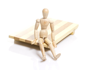 Wooden dummy is sitting on a japan plate for sushi.