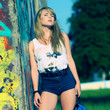 Beautiful young girl stands near wall with graffiti outdoor