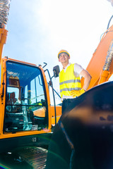 Asian builder in excavator on construction site