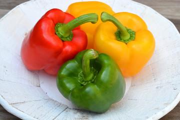 Verse gekleurde paprika's op een houten bord