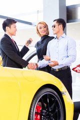 Asian couple buying car in dealership