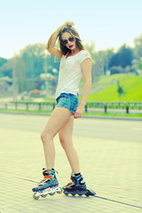 Beautiful girl sitting on the road in roller skates