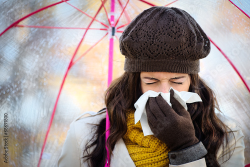 Woman coughing and blowing her nose in autumn - 68691800