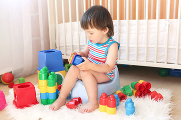 lovely baby boy plays toys sitting on potty