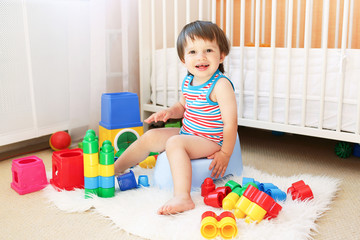 baby with toys sitting on potty