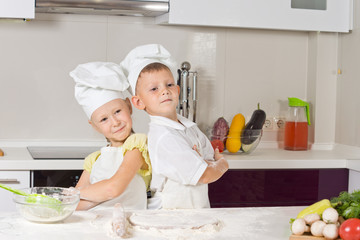 Girl and boy in the kitchen, posing back to back