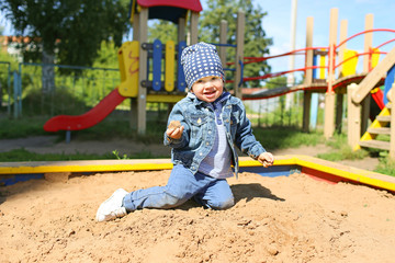 happy little boy playing with sand on playground