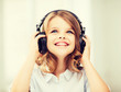 canvas print picture - little girl with headphones at home
