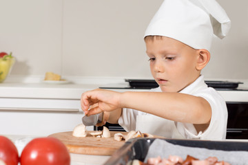 Cute little boy in a chefs toque slicing mushrooms