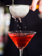 Bartender pooring cocktail into Martini glass