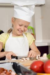Happy little girl in a cooks uniform