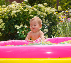 Funny little boy playing with water in baby pool