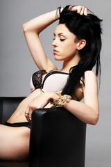 Sensual brunette with black and beige underwear sitting on sofa
