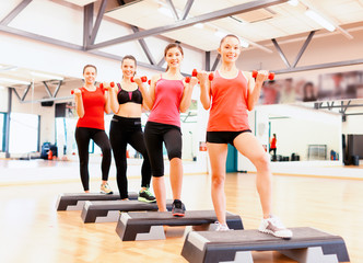 group of smiling female with dumbbells and step