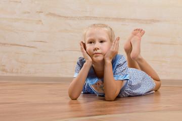 Bored little girl lying on the wooden floor