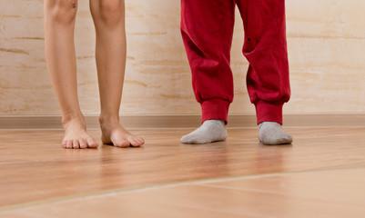 Two Little Kids Feet on Wooden Floor