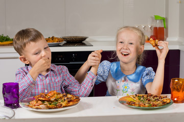 Two children celebrating eating their pizza