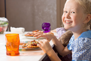 Laughing little girl eating homemade pizza