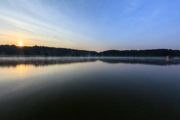 Sonnenaufgang am Ufer vom See