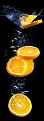 slice of orange in the water with bubbles