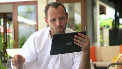 Man with tablet computer drinking coffee in the morning