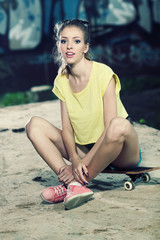 Ordinary girl hipster sitting on a skateboard and enjoys life