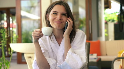 Woman talking on cellphone, drinking coffee by table