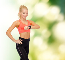 smiling woman with heart rate monitor on hand