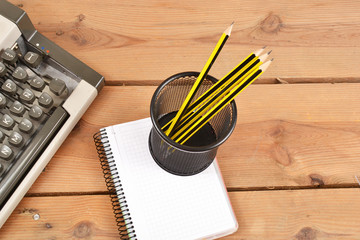 Typewriter, notebook and pencils