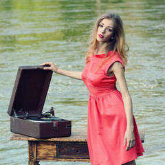 Stylish  fashion girl listening to retro gramophone