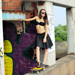 Sexy girl in  skirt posing with a skateboard