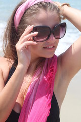Attractive brunette young woman posing sexy at the beach
