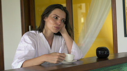 Pensive beautiful woman drinking coffee at home