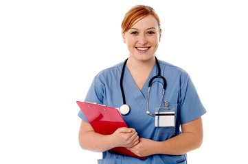Young female nurse holding clipboard