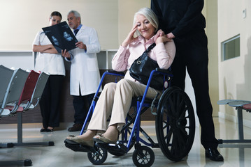 Senior woman on wheelchair with her husband and doctors analyzin