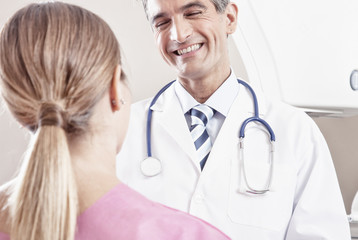 Happy young male doctor speaking with female patient undergoing