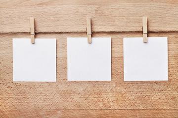 Drei Notizzettel vor braunem Holzhintergrund