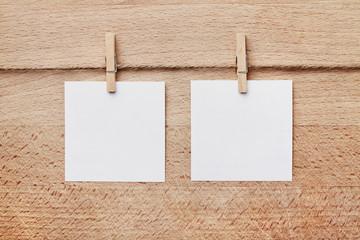 Zwei Notizzettel vor braunem Holzhintergund