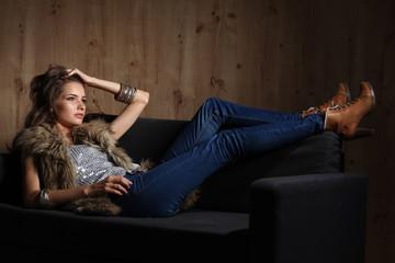Portrait of elegant woman sitting on black sofa wearing a blue