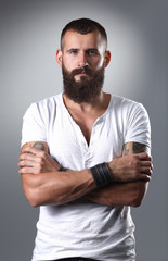 Portrait of handsome bearded man standing with crossed arms,