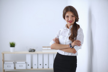 Attractive businesswoman with her arms crossed  standing in off