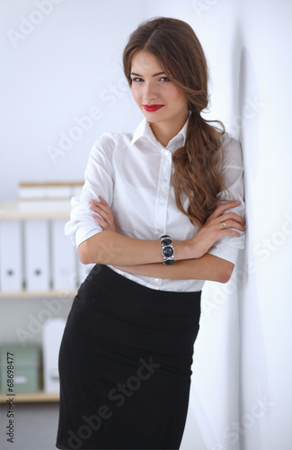 canvas print picture Attractive businesswoman with her arms crossed  standing in off