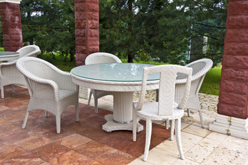 White table and chairs patio furniture in a garden's gazibo.