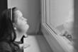 femme regarde par la fenêtre