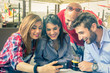 Friends looking at mobile phone in a bar