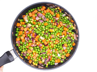 Frying vegetables in a fry pan, peas, red onion, carrot and corn