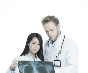 Caucasian male doctor examining x-ray with female assistant. Iso